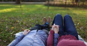 two people laying in grass holding hands